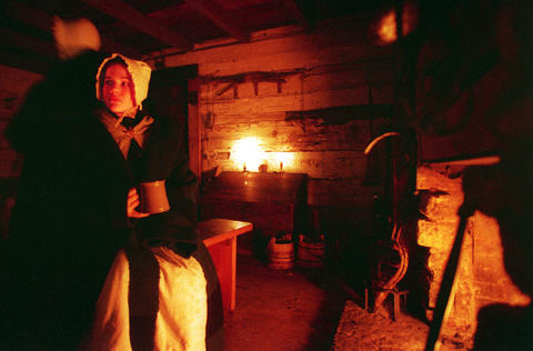 Dec. 23, 1999: Colleen Metzger plays a 19th century settler at Naper Settlement during holiday festivities. Sitting by the fireplace at a log house on the premises, she gave visitors an idea of what Christmas would have been like during that period.