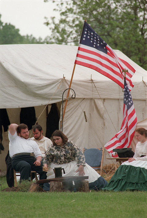 """May 15, 1999: Sitting in """"Camp Douglas"""" with flags flying and waiting for the water to boil over an open campfire, Angela Gunder, second from right, adds hay to the fire during Civil War Days at Naper Settlement."""