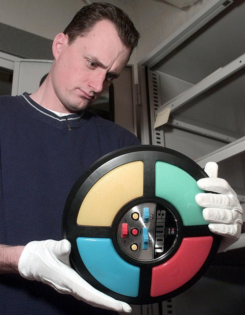 Nov. 3, 1999: Will Buhlig examines a Simon Says game, which is part of an exhibit at the Pre-Emption House featuring memorabilia from every decade of the 1900s.