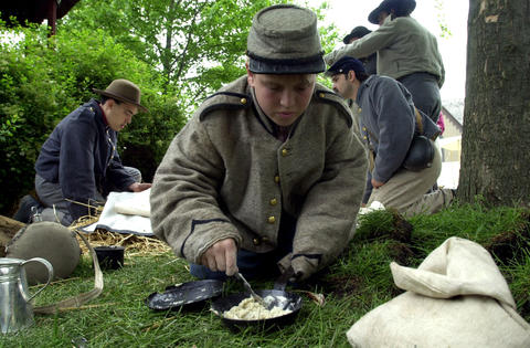 May 20, 2000: Civil War reenactor Calvin Sorchy, 14, makes Johnnycakes over an open fire at Naper Settlement.