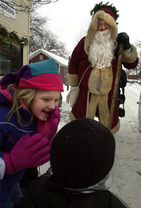 """Dec. 27, 2000: Tabitha Lavin, 6, whispers to her brother Peyton, 4, on what to tell """"Father Christmas,"""" played by Kurtis Weems, while visiting Naper Settlement during the Christmas Memories event. During the event, visitors met Scrooge, Father Christmas, took a carriage ride, enjoyed entertainment, made crafts and participated in other activities."""