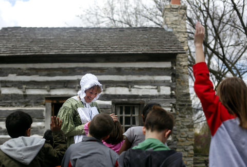 May 6, 2011: Mary Anne Obal, a museum educator, talks with a group of children in front of the Log House at Naper Settlement.
