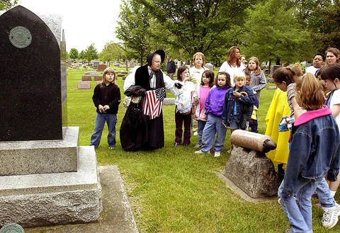 May 23, 2002: Museum educator Phyliss Goerling, at center with flag, shows a Civil War monument to a Brownie troop from the Georgetown School in Aurora.