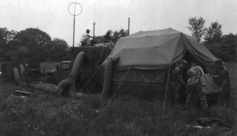 Aug. 29, 1997: The Psychological Operations Battalion out of Joliet, a one-of-a-kind Special Operations Medical Systems Unit, assemble their equipment for field training at the old Joliet Arsenal. The tent was a portable radio and TV studio/unit. This was the only Army reserve unit in the country that served as a radio and TV broadcast unit.