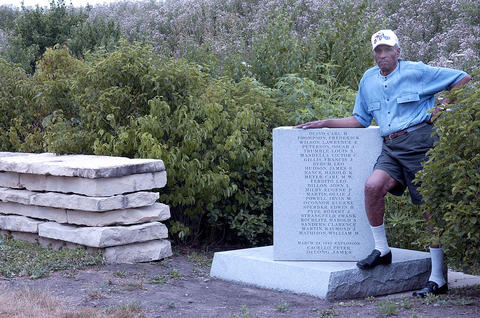 July 12, 2005: Elmo Younger, 83, of Morris, stands next to the base of the monument that held the stolen statue, which was near the entrance to the Abraham Lincoln National Cemetery in Elwood. Younger worked at the plant, and while he was not present during the blast, he took it upon himself to make sure those who worked at the plant were honored. Upon his retirement in 1987, Younger was appointed to the Joliet Army Ammunition Plant Restoration Advisory Board, which received $40,000 from the state and other contributors to erect the monument in 2001. Younger also raised funds to replace the stolen statue, and was stunned when he received a call that the stolen statue had been found on a farm near Braceville, Ill., in 2008.