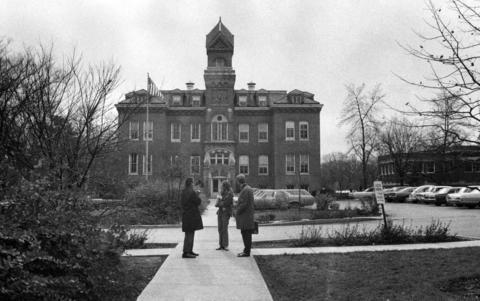 """November 1970: Dr. T. Howard Krueger, left, professor of music, Judy Kalkbrenner, center, and Jim Sorensen, assistant professor of music, stand in front of """"Old Main,"""" the oldest building on the Elmhurst College campus."""