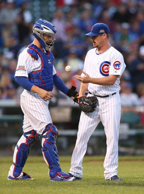 Cubs starting pitcher Travis Wood and catcher John Baker meet on the mound in the second inning.