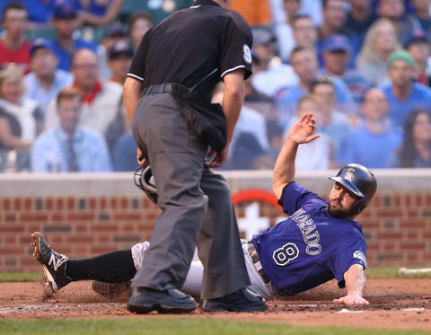 The Rockies' Michael McKenry slides in safely at home as he scores on a double by Charlie Culberson in the second inning.