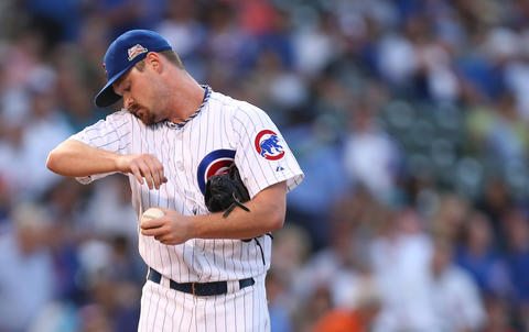 Cubs starting pitcher Travis Wood reacts after giving up a run-scoring single to the Rockies' Justin Morneau in the first inning.