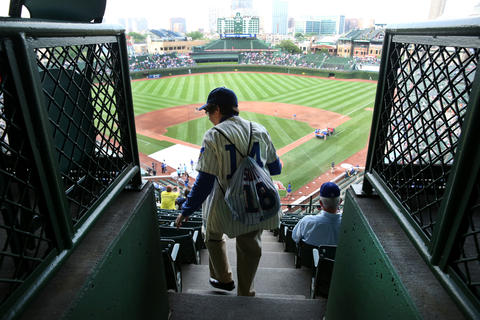 A woman walks down stairs while trying to find her seat in the upper deck at Wrigley Field.
