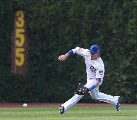 Cubs left fielder Chris Coghlan fields a run-scoring single hit by the Rockies' Justin Morneau in the first inning.