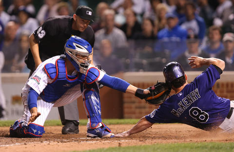 Cubs catcher John Baker with the play on the Rockies' Michael McKenry at home plate in the 10th inning.