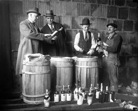 Capt. A. C. Townsend, from left, U. S. Marshall Palmer Anderson, Dept. U. S. Marshall A. J. Jostock and a laborer look over confiscated liqour at the federal warehouse, circa April 20, 1925. Townsend and the men were ordered to clear out the Federal government warehouse for seized liquor to make room for army purposes.