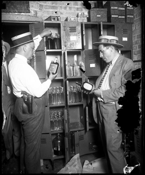 Capt. A. C. Townsend, left, and agent Joseph J. Wahl look over booze confiscated during a raid in August of 1925. Editors note: this negative is damaged.