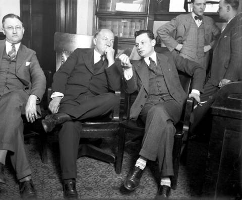 Millionaire bootlegging lawyer, George Remus, center, and his Attorney Harry N. Pritzker, circa June 27, 1928. Remus was one of the biggest dealers in illegal whiskey in the United States. Remus was fighting a murder charge because he killed his wife, Imogene Remus, in 1927 after he was released from prison. While Remus had been in prison, Imogene stole all of Remus' money, hired a hit man to kill him, and ran off with an undercover Prohibition agent.