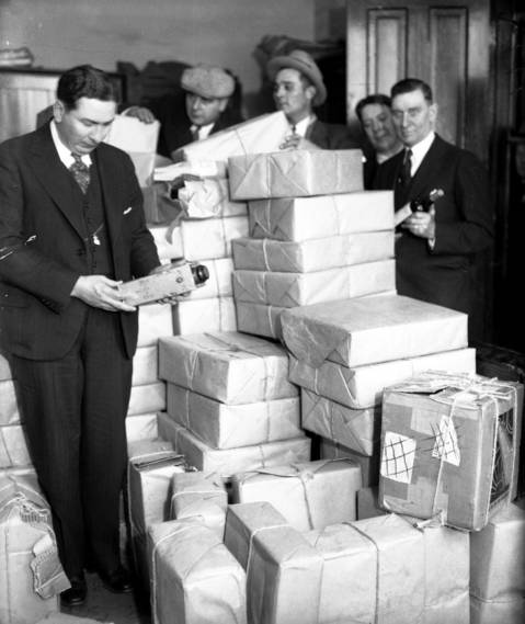 Captain Richard Gill, from left, and Sergeants T. T. Barnes, John Kratzmeyer, Tom Ryan and Phil Cassin, inspect the fruits of their raid on the A. R. Thompson warehouse at 213 E. Illinois St. , circa Dec. 2, 1930. It's $5,000 worth of Capone's liquor neatly wrapped to look like stationary.
