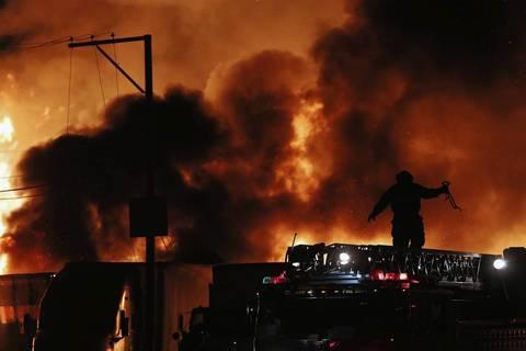 A firefighter walks atop an truck as the fire burns behind him.