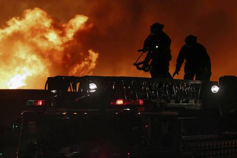 Firefighters secure equipment at the flames rage.