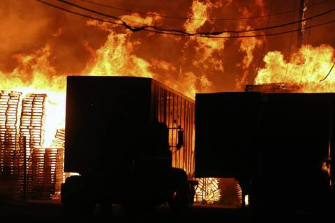 Flames rise above trucks and stacks of pallets.