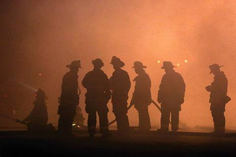 Chicago firefighters are silhouetted against smoke.