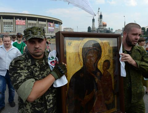 "Men in military dress hold an icon of the Mother of God during a rally in support of the self-proclaimed ""People's Republics of Donbass and Luhansk"", in Moscow."