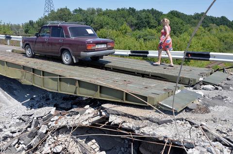 People cross a damaged bridge in their car on near the village of Debaltseve, in the Donetsk region, eastern Ukraine.
