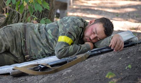 A Ukrainian serviceman sleeps at a checkpoint near the eastern Ukrainian city of Debaltseve in the Lugansk region.
