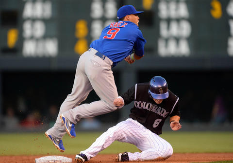 Javier Baez turns a double play over the Rockies' Corey Dickerson in the second inning.