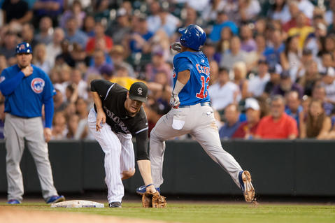 Starlin Castro reaches first base with a single as the throw pulls the Rockies' Justin Morneau off the bag in the sixth inning.