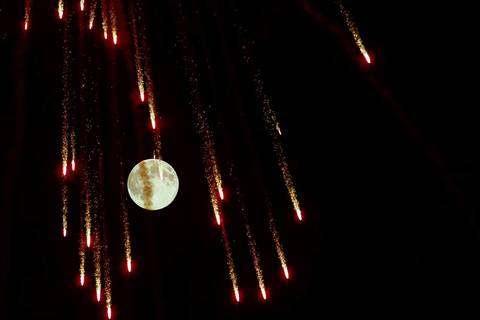 Fireworks streak in front of the supermoon outside the town of Mosta in central Malta.