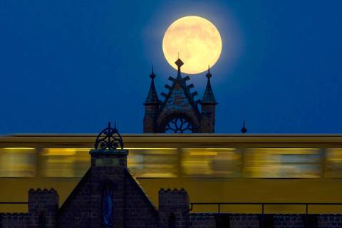 The supermoon rises behind Oberbaum Bridge as a train passes through in Berlin.
