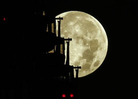 The supermoon is seen behind a ferris wheel in Tokyo.