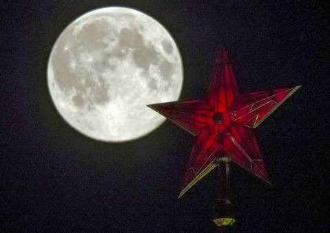 The supermoon rises over the stars of Moscow's Kremlin towers.