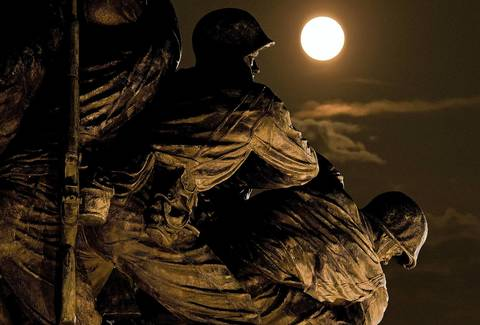 A supermoon rises above the U.S. Marine Corps War Memorial in Arlington, Va.