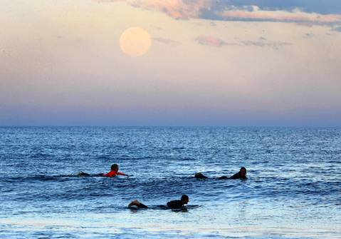 Surfers wait for waves as a supermoon rises off the Sydney, Australia, suburb of Wanda.