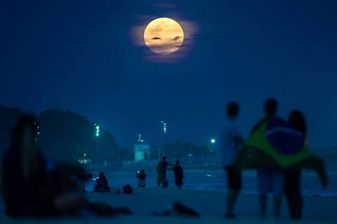 Beachgoers in Rio de Janeiro, Brazil, watch the supermoon on Sunday.