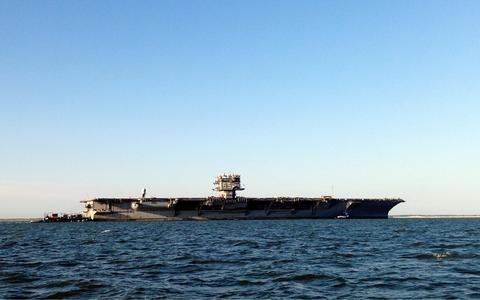 The USS Enterprise is towed from Naval Station Norfolk to the Newport News shipyard where it will be decommissioned.