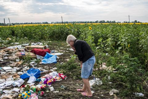 2014, July 19 - RASSIPNOYE, UKRAINE - A woman looks at debris from Malaysia Airlines flight MH 17 which crashed in a field of sunflowers on July 19, 2014 in Rassipnoye, Ukraine. Malaysia Airlines flight MH17 was traveling from Amsterdam to Kuala Lumpur when it crashed killing all 298 on board including 80 children. The aircraft was allegedly shot down by a missile and while investigations continue to confirm the perpetrators of the attack economic and travel sanctions have been imposed on Russia by western nations including the United States.