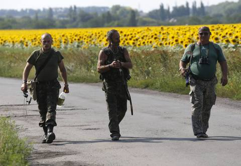 2014, August 04 - KIEV, UKRAINE - Pro-Russian separatists walk near sunflower fields at the site of the downed Malaysian airliner MH17 near the village of Rozsypne in the Donetsk region August 4, 2014. Ukrainian government forces recaptured an important railway hub from pro-Russian rebels in the east of the country, with five soldiers killed and 15 others wounded in the previous 24 hours, said a security official in Kiev.