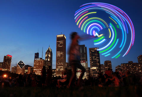 A dancer moves to the music with an LED hula hoop during the Chicago Blues Festival in Grant Park.
