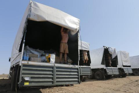 Drivers of a Russian convoy of trucks carrying humanitarian aid for Ukraine show the contents of their trucks at a camp near Kamensk-Shakhtinsky.
