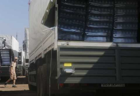 A driver walks past Russian convoy of trucks carrying humanitarian aid for Ukraine at a camp near Kamensk-Shakhtinsky.