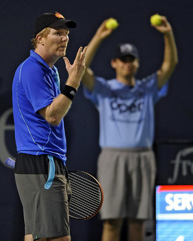 Jim Courier blows on his fingers after making a nice passing shot against James Blake during an exhibition game on day four of the 2014 Connecticut Open Tennis Tournament at the Connecticut Tennis Center on the Yale campus in New Haven Wednesday evening. Blake won 7-5, 6-3.
