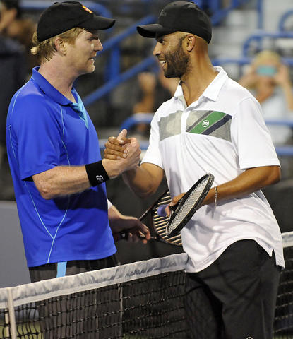 Jim Courier and James Blake shake hands after playing an exhibition game on day four of the 2014 Connecticut Open Tennis Tournament at the Connecticut Tennis Center on the Yale campus in New Haven Wednesday night. Blake won 7-5, 6-3. Tomorrow night Balke will play Andy Roddick.
