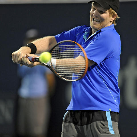 Jim Courier returns a shot from James Blake during an exhibition game on day four of the 2014 Connecticut Open Tennis Tournament at the Connecticut Tennis Center on the Yale campus in New Haven Wednesday evening.
