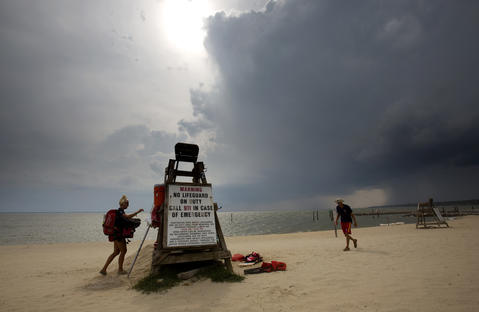 Newport News lifeguard Emily Townsend and Lt. Guard Kurt Fortner gather their gear from the guard station after closing Huntington Beach due to lightening during the approach of an afternoon storm Tuesday afternoon.