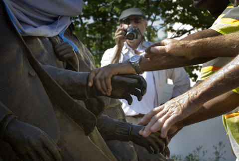 "Workers grab statue hands from the ""The Unfinished March"" as artist Ed Hamilton records the installation process Tuesday at Martin Luther King, Jr. Plaza in Newport News."