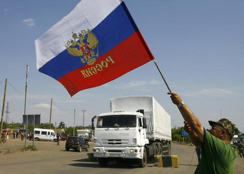 A local resident holds a Russian national flag as part of a Russian humanitarian convoy cross the Ukrainian border at the Izvarino custom control checkpoint.