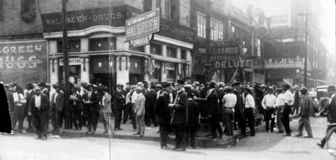 African-American men gather in front of Walgreen Drugs at 35th and State Streets during the 1919 race riots in Chicago. Police officers stand in front of the crowd.