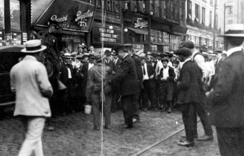 A black man is searched by Chicago Police in front of a crowd at an unidentified spot in Chicago during the 1919 race riots.
